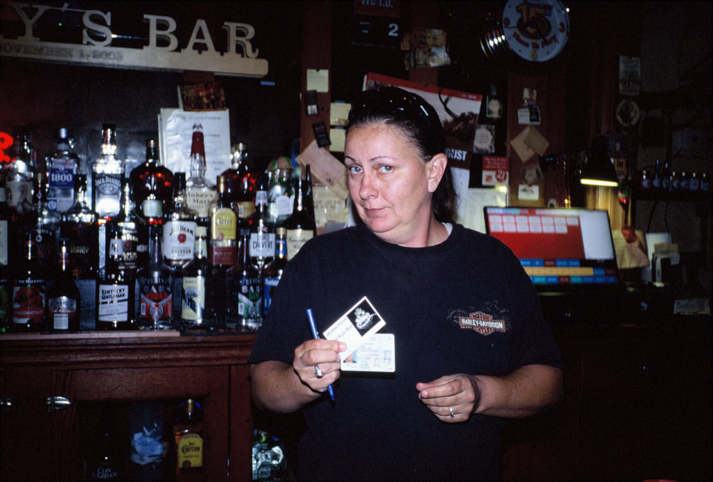 G.I. handing me my membership card to Stinky's Bar in Osceola, KS. Shot with a Kodak VR35 K12. Russell Viers